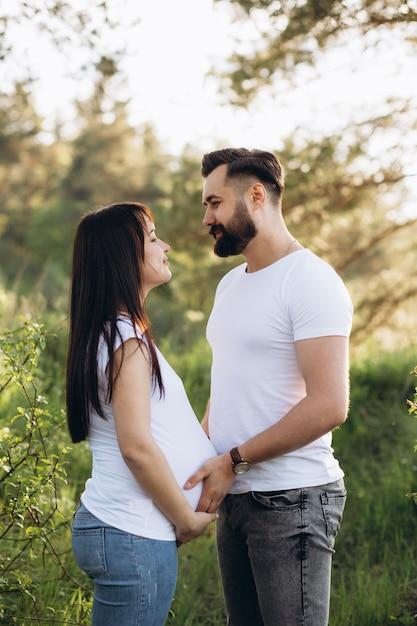 Casal jovem feliz esperando bebê no parque de verão Foto Premium