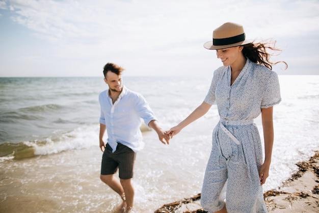 Casal jovem feliz família caminhando na praia de mãos dadas. o conceito de lua de mel e férias de verão Foto Premium