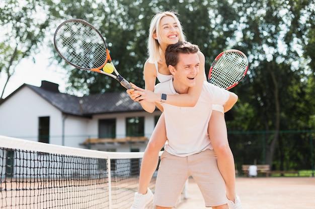 Casal jovem feliz jogando tênis Foto gratuita