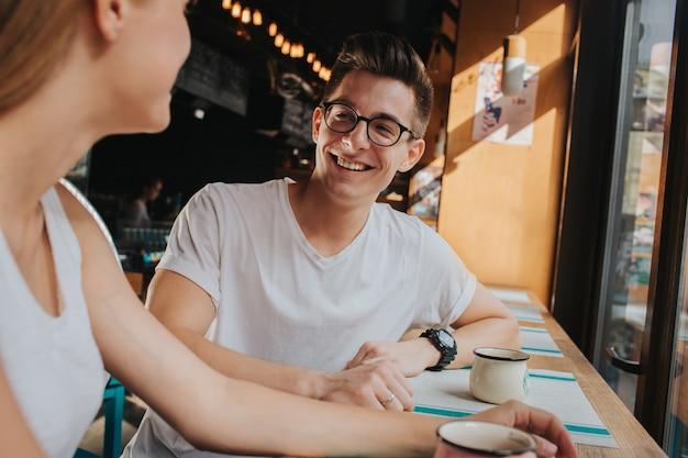 Casal jovem feliz no amor, tendo um bom encontro em um bar ou restaurante. eles contam algumas histórias sobre si mesmos, tomando chá ou café e comendo salada e sopa. Foto Premium