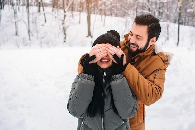 Casal jovem feliz no inverno. família ao ar livre. homem e mulher olhando para cima e rindo. amor, diversão, estação e pessoas - caminhando em winter park. ele cobriu os olhos dela com as mãos Foto Premium