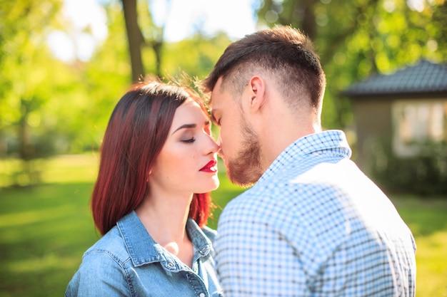 Casal jovem feliz no parque em pé e rindo no dia ensolarado Foto gratuita