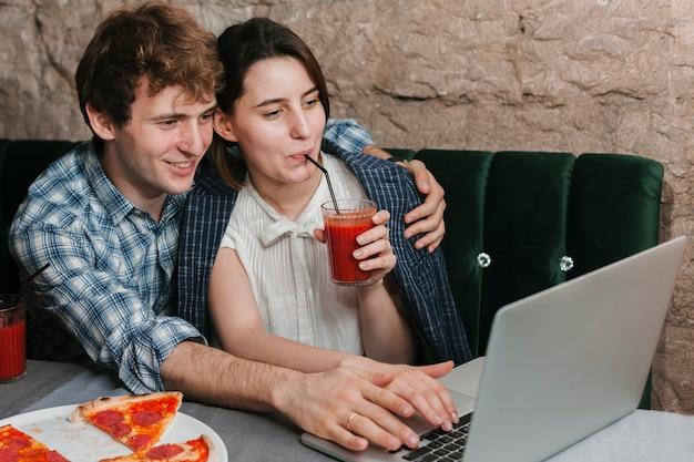 Casal jovem feliz no restaurante olhando para o laptop Foto gratuita
