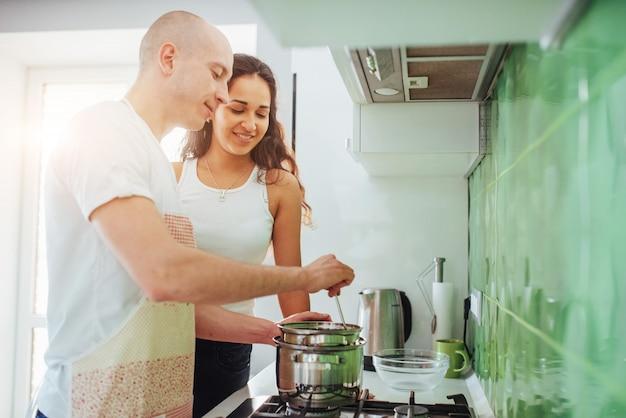 Casal jovem feliz, preparando no fogão Foto Premium