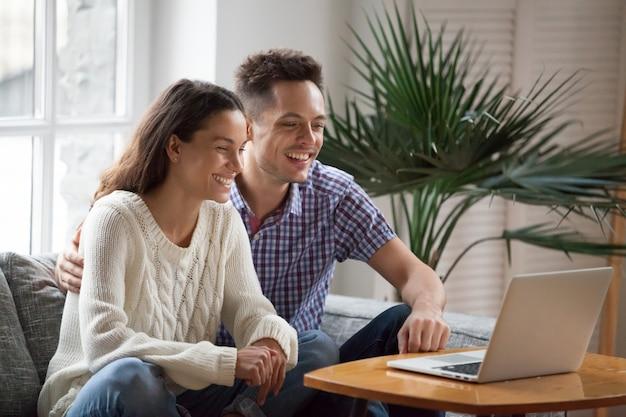 Casal jovem feliz rindo assistindo vídeo engraçado ou fazendo videocall Foto gratuita