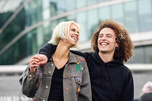 Casal jovem feliz rindo em meio urbano Foto Premium