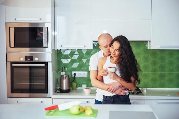 Casal jovem feliz tomando café na cozinha Foto Premium