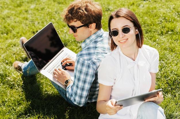 Casal jovem freelancer trabalhando ao ar livre Foto gratuita