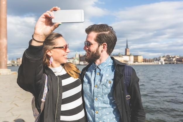 Casal jovem hippie tendo um selfie em estocolmo Foto Premium