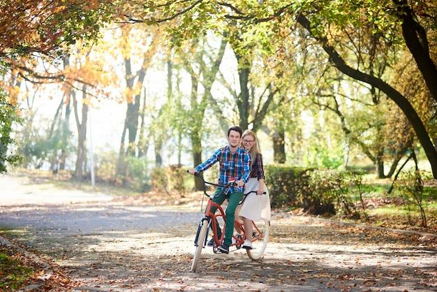 Casal jovem, homem bonito e mulher atraente na bicicleta tandem no parque ensolarado de verão ou floresta. Foto Premium