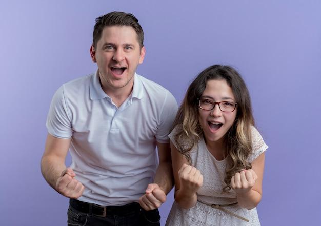 Casal jovem, homem e mulher, olhando para a câmera cerrando os punhos, feliz e animado em pé sobre a parede azul Foto gratuita