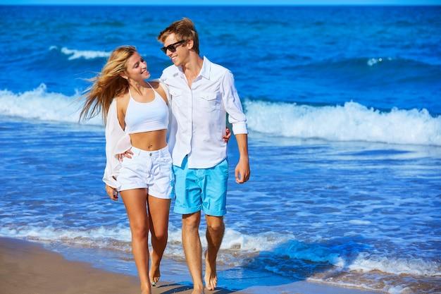Casal jovem loiro andando na praia Foto Premium
