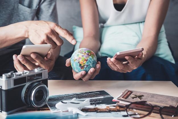 Casal jovem, planejando a viagem de férias e pesquisando informações ou reserva de hotel em um telefone inteligente Foto Premium
