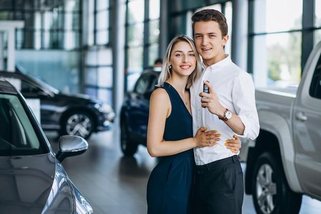 Casal jovem, revendo um carro em uma sala de exposições Foto gratuita