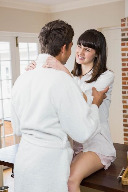 Casal jovem romântico, abraçando um ao outro na cozinha Foto Premium