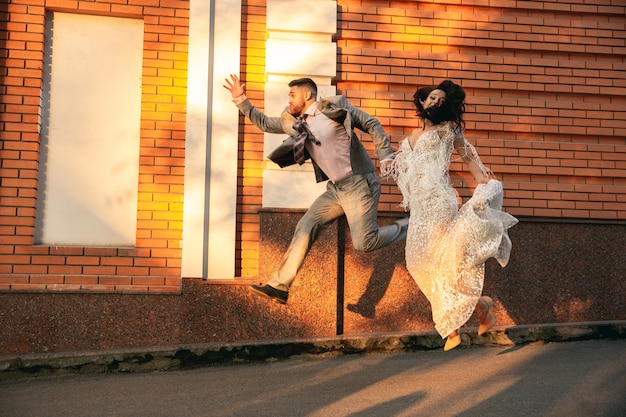 Casal jovem romântico caucasiano celebrando o casamento na cidade. concurso noiva e noivo nas ruas da cidade moderna. família, relação, conceito de amor Foto gratuita
