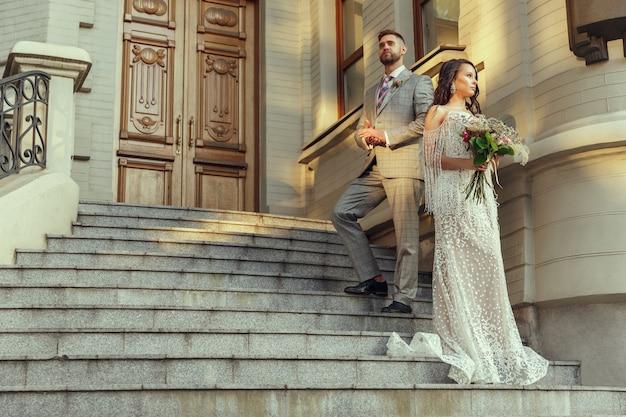 Casal jovem romântico caucasiano celebrando seu casamento na cidade. Foto gratuita