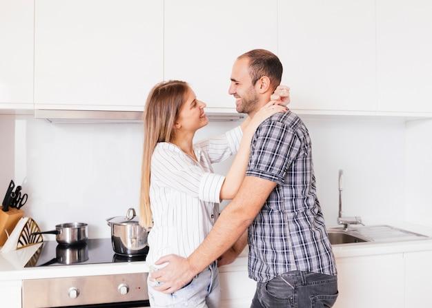 Casal jovem romântico em pé na cozinha olhando um ao outro Foto gratuita
