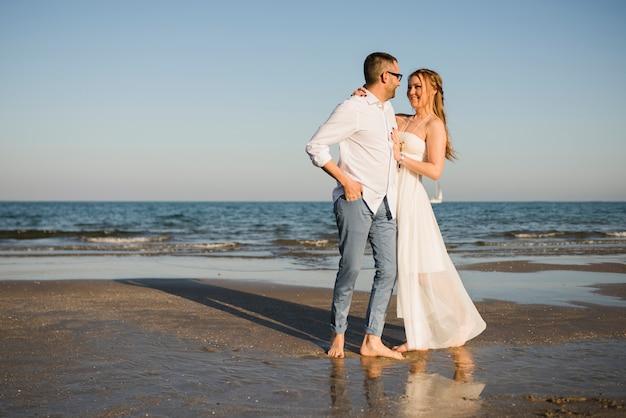 Casal jovem romântico olhando uns aos outros em pé perto do mar na praia Foto gratuita