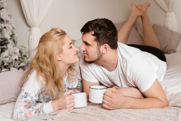 Casal jovem romântico tomando café na cama Foto gratuita
