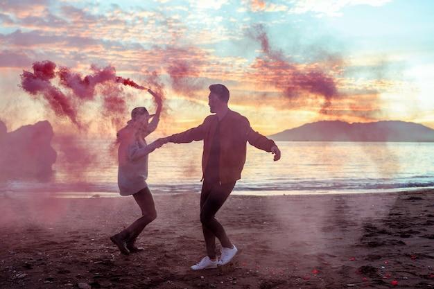 Casal jovem se divertindo com bomba de fumaça rosa na costa do mar Foto gratuita