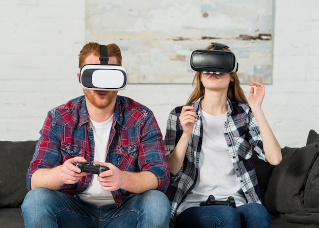 Casal jovem sentado no sofá durante a experiência vr jogando o joystick Foto gratuita