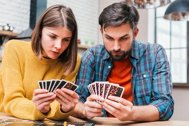 Casal jovem sério olhando suas cartas jogando o jogo de tabuleiro Foto gratuita