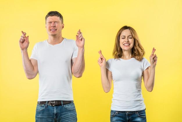 Casal jovem sorridente cruza os dedos em antecipação de algo agradável Foto gratuita