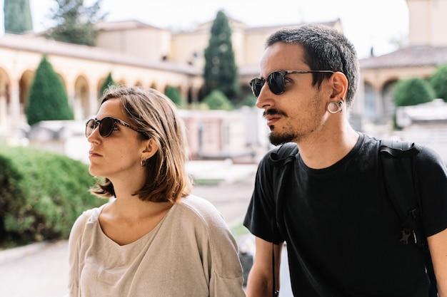 Casal jovem triste com óculos de sol virado para a frente no cemitério de bolonha, itália Foto gratuita