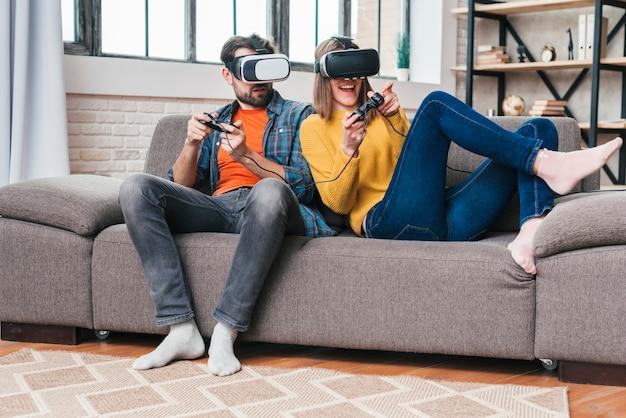 Casal jovem usando óculos de realidade virtual, jogando o jogo de vídeo Foto gratuita