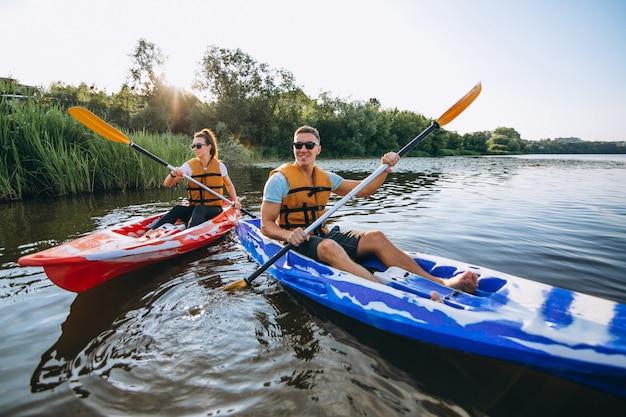 Casal juntos de caiaque no rio Foto gratuita
