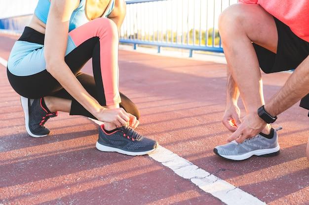 Casal latino-americanos, amarrando seus sapatos de treinador depois de correr juntos ao ar livre. Foto Premium