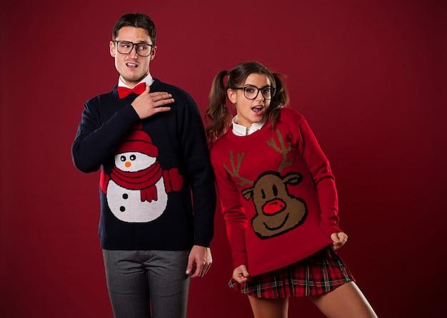 Casal louco de nerds em suéteres engraçados brincando Foto gratuita