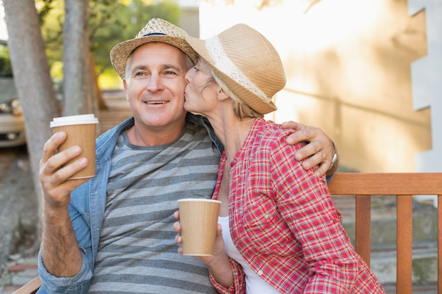 Casal maduro feliz bebendo café em um banco na cidade Foto Premium