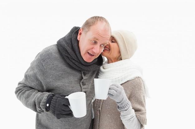 Casal maduro feliz em roupas de inverno segurando canecas Foto Premium
