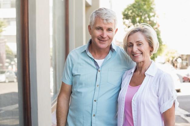 Casal maduro feliz sorrindo para a câmera na cidade Foto Premium