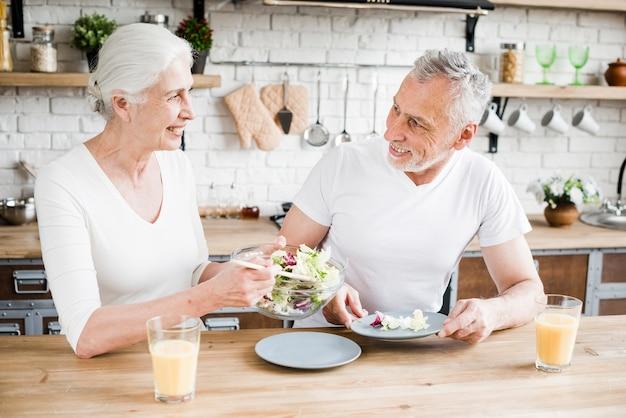 Casal mais velho cozinhando na cozinha Foto gratuita