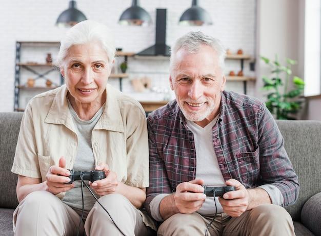 Casal mais velho jogando videogame juntos Foto gratuita