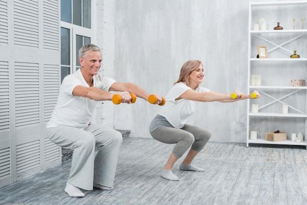 Casal mais velho sorridente, realizando exercícios com halteres em casa Foto gratuita