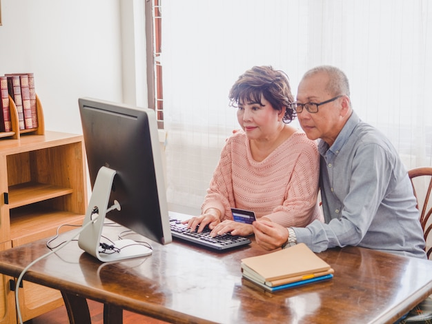 Casal mais velho usando o computador em conjunto com cartão de crédito em casa Foto Premium