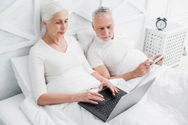 Casal mais velho usando um laptop Foto gratuita