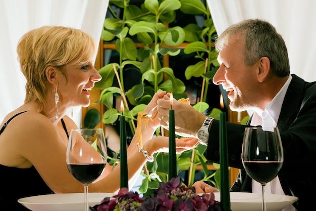 Casal maturo comendo um jantar romântico em um restaurante chique Foto Premium