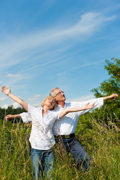 Casal maturo se divertindo em um campo ensolarado Foto Premium