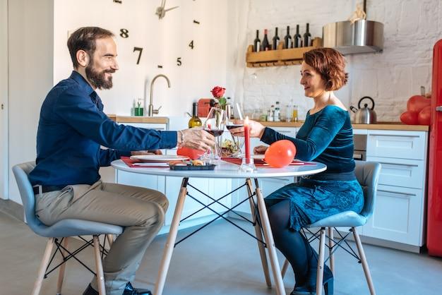 Casal maturo, tendo um jantar romântico em casa no dia dos namorados e fazendo torradas com vinho tinto Foto Premium