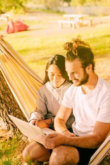 Casal moderno relaxante juntos na rede ao ar livre Foto gratuita