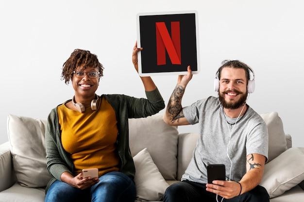 Casal mostrando um ícone da netflix Foto gratuita