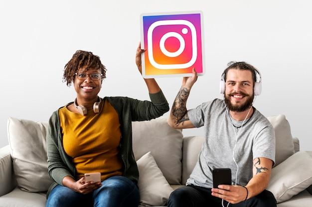 Casal mostrando um ícone do instagram Foto gratuita