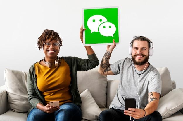 Casal mostrando um ícone do wechat Foto gratuita