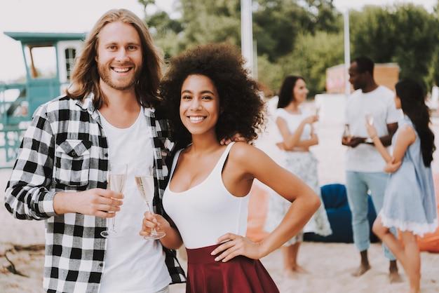 Casal multirracial bebendo champanhe na praia Foto Premium