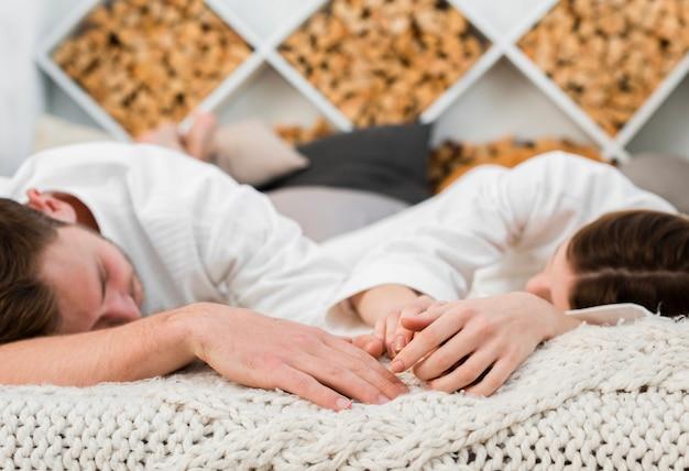 Casal na cama dormindo enquanto vestindo roupões de banho Foto gratuita